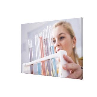 Teenage girl holding rack of test tubes canvas print