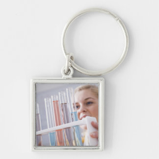 Teenage girl holding rack of test tubes keychain