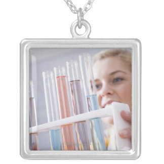 Teenage girl holding rack of test tubes silver plated necklace