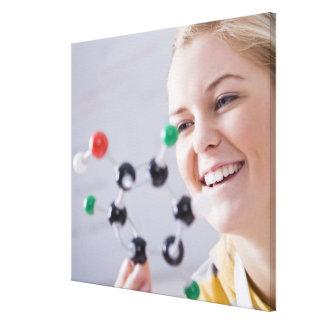 Teenage girl looking at molecule model canvas print