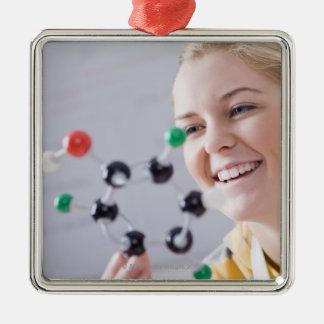 Teenage girl looking at molecule model metal ornament