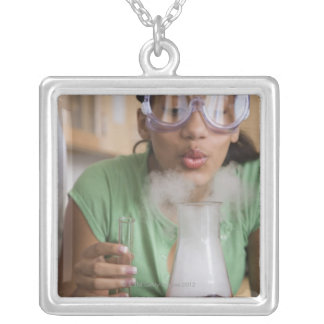 Teenage girl performing science experiment silver plated necklace