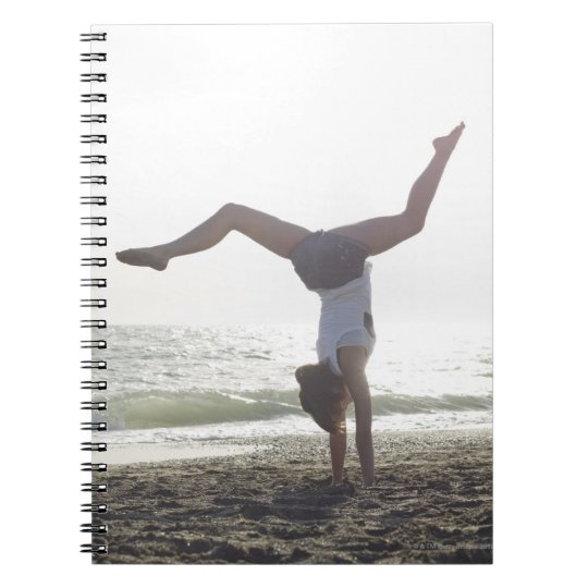 Teenage girl performs gymnastic feat, mom spiral notebook