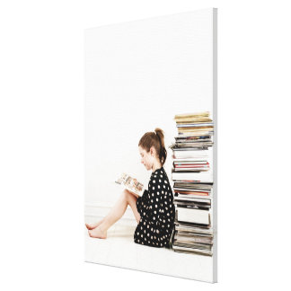 Teenage girl reading comic strip by pile of canvas print