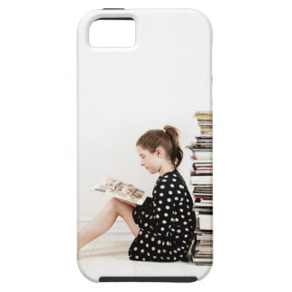 Teenage girl reading comic strip by pile of iPhone SE/5/5s case