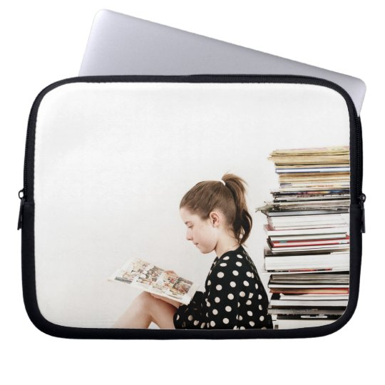 Teenage girl reading comic strip by pile of laptop sleeve