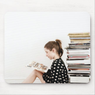 Teenage girl reading comic strip by pile of mouse pad