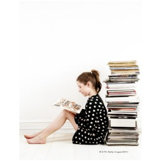 Teenage girl reading comic strip by pile of post card