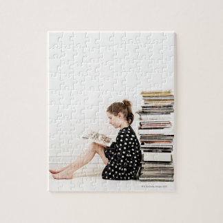 Teenage girl reading comic strip by pile of jigsaw puzzles