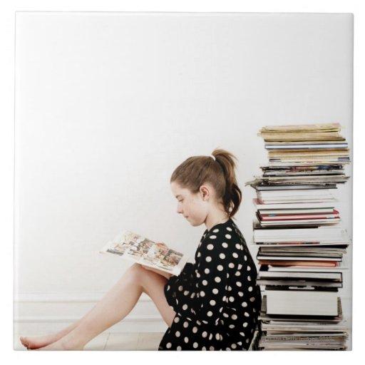 Teenage girl reading comic strip by pile of ceramic tile