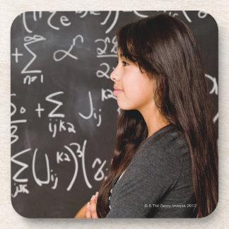 Teenage girl student at blackboard with math coasters