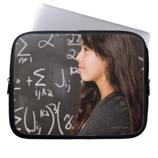 Teenage girl student at blackboard with math laptop sleeves