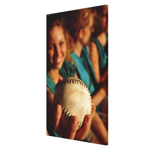 Teenage girls' softball team sitting in dugout canvas print