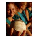 Teenage girls' softball team sitting in dugout postcard