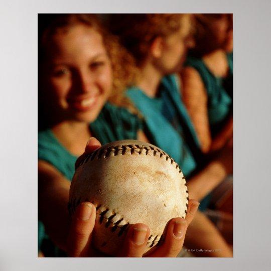 Teenage girls' softball team sitting in dugout poster
