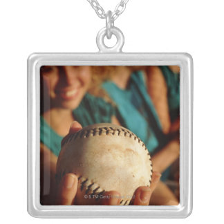 Teenage girls' softball team sitting in dugout square pendant necklace