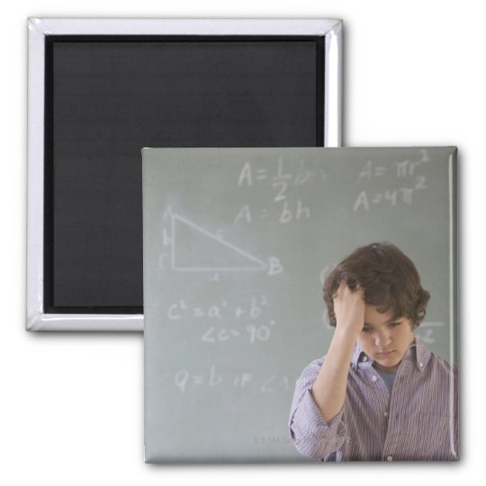 Teenaged boy in front of blackboard with math 2 inch square magnet