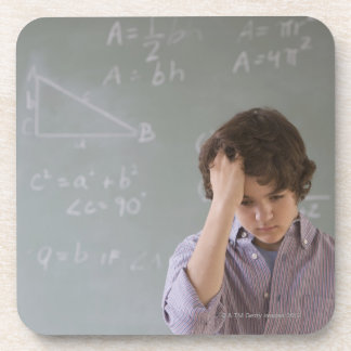 Teenaged boy in front of blackboard with math drink coaster