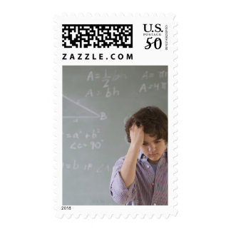 Teenaged boy in front of blackboard with math postage