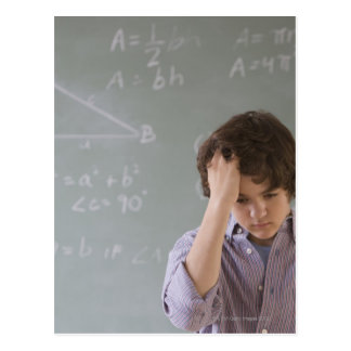 Teenaged boy in front of blackboard with math postcard