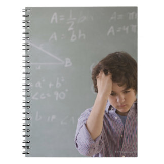 Teenaged boy in front of blackboard with math spiral notebook