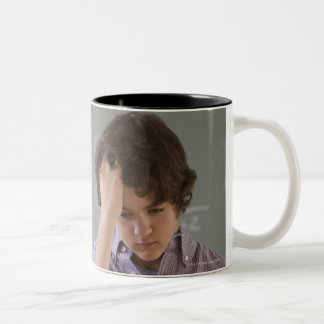 Teenaged boy in front of blackboard with math Two-Tone coffee mug