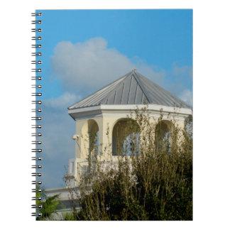 tejado del chapitel contra el cielo azul y los libro de apuntes con espiral