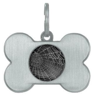 Tela de araña con las gotas del agua placas de nombre de mascota