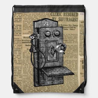 Teléfono antiguo en la mochila del lazo del papel