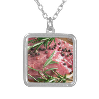 Tenderloin of raw beef with herbs and spices silver plated necklace