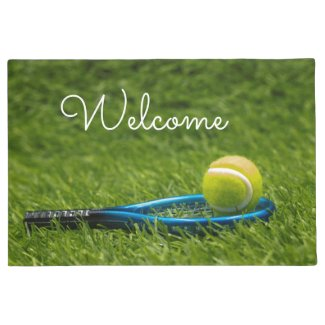 Tennis ball is on green grass with love welcome doormat