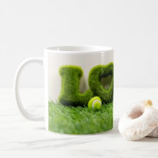 Tennis ball with love letter on green grass coffee mug