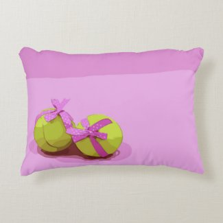 Tennis ball with pink ribbon on pink accent pillow