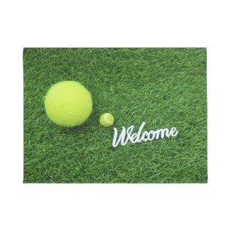 Tennis balls are on green grass welcome Bath Mat