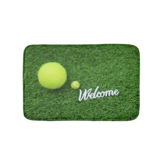 Tennis balls are on green grass welcome bath mat