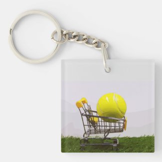 Tennis balls in shopping trolley on green grass keychain