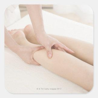 Terapeuta del masaje que aplica masaje del pie pegatina cuadrada