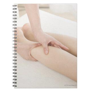 Terapeuta del masaje que aplica masaje del pie spiral notebooks