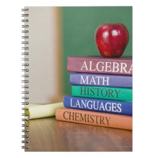 Textbooks and an apple 2 spiral notebook