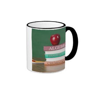 Textbooks and an apple ringer coffee mug
