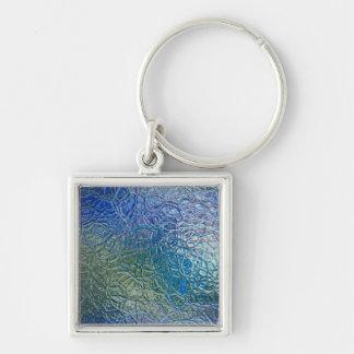 Textura de cristal coloreada, superficie brillante llavero cuadrado plateado