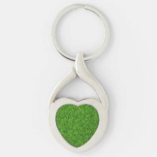 Textura de la hierba verde llavero plateado en forma de corazón