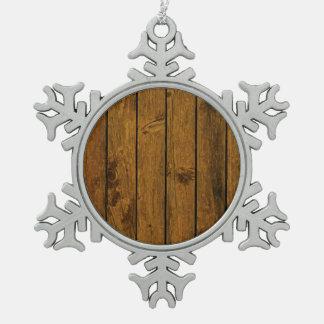 Textura de madera marrón resistida de la pared adorno de peltre en forma de copo de nieve