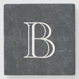 Textura de piedra negra elegante del monograma posavasos de piedra