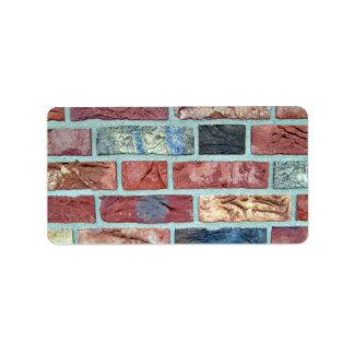 Textura de una pared de ladrillo coloreada etiqueta de dirección