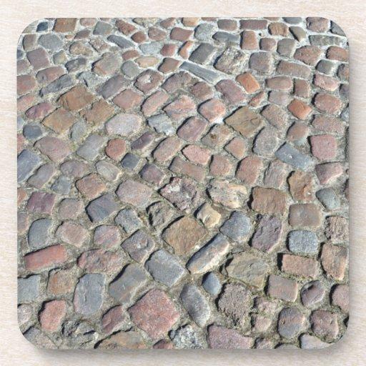 Textura del primer del pavimento de piedra viejo posavasos