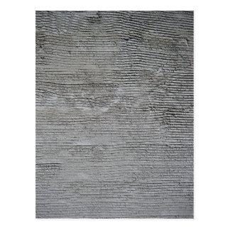 Textura gris áspera del muro de cemento con las lí postales