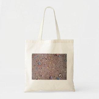 Textura roja de la arena con las piedras bolsa de mano