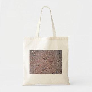 Textura roja de la arena con las piedras bolsa