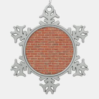 Textura roja de la pared de ladrillo adorno de peltre en forma de copo de nieve